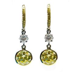 Fancy Yellow Diamond Gold Drop Earrings. These 3.02Ctw stunning fancy yellow Vvs2 clarity round brilliant diamonds are bezel set and hang delicately from two cushion cut diamonds weighing 0.40ctw. Set in 18KT yellow gold and accented by 0.18ctw of fancy yellow pave, c 2014