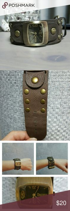 """Vegan  Fashion Watch Faux pebbled leather.  Gold Toned studs accent sides of strap.  Deep gold toned frames the face of the watch with a brushed look.   Deep brown colored face on watch, with gold tone numbers and hands.  1.25"""" wide band,  9"""" long   Tip of strap is beginning to come separated, but not noticeable when wearing- see last picture.   Offers welcome!  Pet free/  smoke free home. Decree Accessories Watches"""