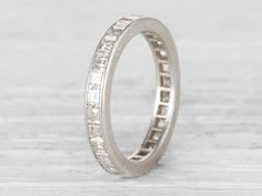 Vintage eternity band set with 28 carré-cut diamonds weighing approximately 2.50 carats total. Set in platinum. Engraved with date. Circa 1966. Vintage wedding bands are hard to find, especially in such an accessible size! This band looks lovely alone or as part of a stack. Diamond and gold mining has caused devastation in areas such as Africa, wreaking havoc on delicate ecosystems and communities. Choosing to go vintage, you are eliminating the need for more mining and lessening the demand…
