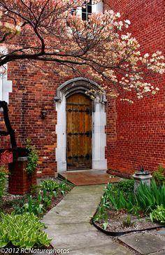 Red brick tones; medieval or Arts & Crafts Movement door
