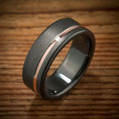 This black zirconium men's wedding band also has a rose gold inlay that will coordinate beautifully with a rose gold wedding ring for the bride. #GoldWeddingRingsForMen