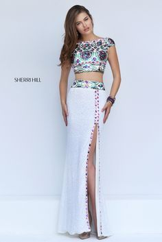 Dress for excitement in the dynamic Sherri Hill 50021 two-piece prom dress. The midriff revealing crop top dazzles in a brilliantly beaded design and showcases a bateau neckline framed with cap sleeves and a V-back. A wide beaded band accentuates the waistline of the full-length fitted skirt with inset sweep train. Beaded trim runs horizontally from the waistline and edges the daring mid-thigh front-side slit.