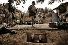 A jounalist climbs out  of the hole where toppled dictator Saddam Hussein was captured in Ad Dawr,  Iraq, near his hometown of Tikrit, Dec. 15, 2003.