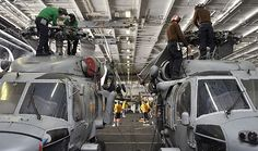 Sailors assigned to the Saberhawks of Helicopter Maritime Strike Squadron (HSM) 77 perform maintenance on the rotors of two MH-60R Sea Hawk helicopters in the hangar bay of the Nimitz-class aircraft carrier USS Abraham Lincoln (CVN 72).