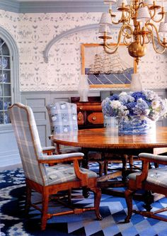 Blue and white hydrangeas blend right into this dining room.  The lush arrangement of hydrangeas and white flowers blends seamlessly with the decor of this dining room, keeping the monochromatic theme working.  Personally I'd have added some red or orange (blue's complementary color) for more energy.