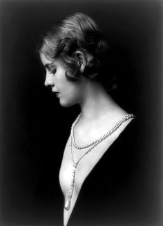 Portrait of Ziegfeld Follies girl Caja Eric wearing a low cut dress with long pearl drop necklace,  1920s Ziegfeld Follies