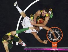 Tunisia's Makram Ben Romdhane, center, fights for the ball under the basket with Lithuania's Jonas Valanciunas, left, and Paulius Jankunas during a men's basketball game. Lithuania won and will face Russia in the quarterfinals.