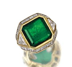 EMERALD AND DIAMOND RING, REPOSSI.  The collet-set step-cut emerald flanked by triangular-shaped diamonds, further enhanced by a step-cut diamond border, mounted in yellow gold,    signed Repossi, Italian assay marks.