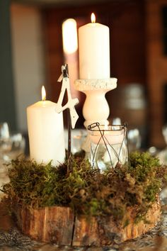For a rustic wedding centerpiece, use a log, some green moss, and candles. Elegant and pretty.
