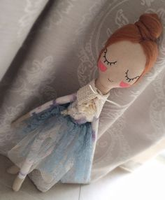 Gorgeous little handmade ballerina rag doll, with lots of detail. Dressed in a pretty lace and tulle dress. Her peaceful and sleepy face is hand embroidered and sure to capture anyones affections. Details:  Approx 54cm tall.  Composition:  •Face, hands, feet- 100% cotton calico •Body- Hand dyed 100% silk dupion •Hair- 100% wool roving •Dress- poly mix lace •Hand knitted scarf- 100% cotton •Filling- 100% polyester Each of Velvet Rainbows dolls has its own character with a special outfit to…