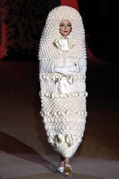 Yves Saint Laurent's knitted cocoon gown in 1965 began a vogue for questioning the very form of the white wedding dress. Did the garment mean to protect or trap the bride? Was she emerging from its depths, metamorphosed into a newly married woman - like a butterfly breaking free from its silk cocoon - or was she being led to her death in a knitted sarcophagus, bound and buried by her new status?