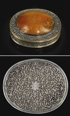 A PARCEL-GILT SILVER FILIGREE AND AMBER-MOUNTED BOX, PROBABLY GOA, 17TH/18TH CENTURY of oval form, decorated with openwork filigree work composed of leafy foliate stems scrolling around a central flowerhead, the lid with ensuite decoration to border surrounding a large inset amber piece, with gilt interior and borders 7.5 by 6.5 by 2.5cm.