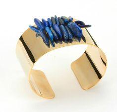 Dans la collection Lapis, retrouvez cette manchette imposante, dorée à l'or fin 16 carats, rehaussée de deux rangs de pierres lapis lazulis.Largeur de la manchette : 4 cm Livré dans sa petite boite cadeau Azucar.  Ces bijoux créateur sont réalisés à la main par la créatrice, dans son atelier situé en région parisienne.  An impressive 16K gold-plated cuff, raised of two rows of lapis lazulis. Cuff width : 4 cmEach jewel is delivered in its Azucar cardbox. This jewel is hand-made in France…