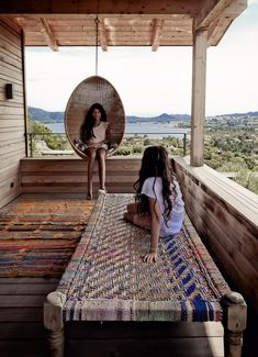 Pattern of wood siding board widths, woven bench, hanging chair, textured rug all overlooking the ocean