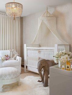 Immagine cameretta da bambini molto elegante, tenui colori rosa e avorio e sofisticato baldacchino per il lettino