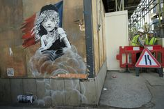 Workmen watch the media photograph a new artwork by British artist Banksy opposite the French Embassy, in London, Monday, Jan. 25, 2016. The artwork depicts the young girl from the musical Les Miserables with tears streaming from her eyes as a can of CS gas lies beneath her. The work is criticising the use of teargas in the refugee camp in Calais. (AP Photo/Alastair Grant)                                     via @AOL_Lifestyle Read more: http://www.aol.com/article/2016/01...