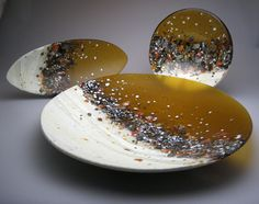 """This bowl is part of a collection of kiln-formed bowls and platters in the Riverstone Series. It is created using compatible sheet glass, custom-created glass """"rock"""" elements, glass frit and 23kt gold foil and requires up to 4 24hr firings at 1450 degrees. Each element is hand placed with careful attention to design resulting in individually unique pieces within the series. 4.5in D x 20.0in diameter $807.50"""