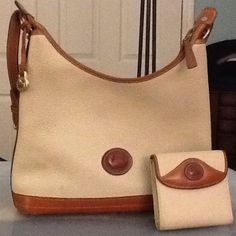 Dooney & Bourke Hobo Style Bag w matching wallet Cream pebbled leather with camel colored trim and D&B logo on front of both bag and wallet.  Brass hardware with brass with D& B logo tag that may be used as a key chain.  Very good condition-minor pen marks and smudges that may be easily cleaned off. Dooney & Bourke Bags Hobos