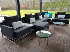 Loungeset Nova zwart met rvs onderstel, hier in een extra grote lounge bank opstelling met ronde salontafels en 2 tussentafels met polywood top. De set heeft 20cm dikke outdoor kussens en kan het hele jaar door buiten blijven staan.