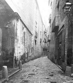 *1908. Una imatge del carrer de l'Avellana captada des de la cruilla amb Graciamat i Riera de Sant Joan. A l'esquerra, entre els dos pilars de pedra del terra, hi havia la font de Sant Joan. (Foto:Arxiu Fotogràfic de Barcelona). BARCELOFÍLIA