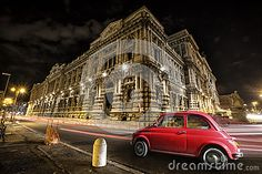 Old car Italian red by night. Italian historic monument. Light trails of car headlights. Palace of Justice, Supreme Court of Cassation and the Judicial Public Library. Rome. Italy.