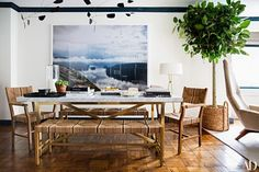 Chairs and benches in woven natural fibers from Serena & Lily help create a casual, inviting atmosphere in the dining area; a tall ficus placed in an oversize Pottery Barn basket completes the look. The white marble-topped table is from Restoration Hardware | archdigest.com