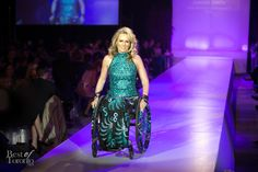A Woman in a Wheelchair on the Runway Models an Elegant Gown by IZ Adaptive