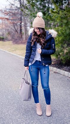 Casual Winter outfit idea.  Navy faux fur hood puffer jacket. White sweater, tan pom pom beanie, ankle booties, tory burch gemini link tote