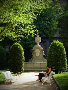 A woman reading inside the garden of the El Prado museum in Madrid  Spain