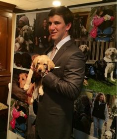 Eli Manning Holds On Tight to a Puppy