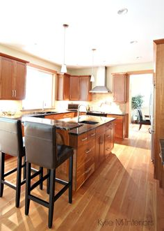 Kitchen with natural cherry cabinets and fir flooring. Island with black granite, raised bar top and travertine tile backsplash