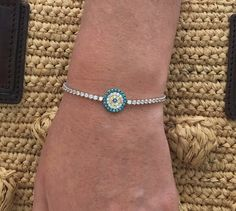 This is an adjustable pave evil eye with CZ stones.  The back is a silver ball which adjusts to every size!  Check out our other hamsa and evil eye jewelry http://www.bettinascollection.com/products/adjustable-evil-eye-pave-disc-with-cz-stones