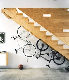Architect Chad Ludeman hangs bicycles beneath the staricase of his affordably built house in Philadelphia.