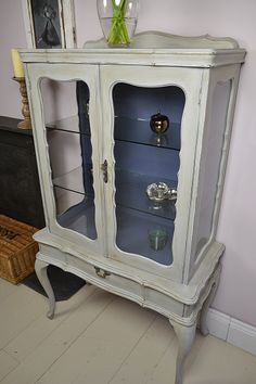 Our Victorian style glass display cabinet is the perfect place to store your ornaments and keepsakes. Hand painted in Annie Sloan Paris Grey with Old Violet painted inside to give an elegant backdrop.