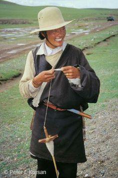 Tibetan man spinning wool on Tibetan road near Nagqu, north of Lhasa, Tibet, China