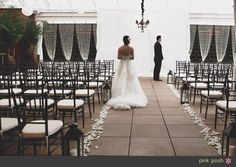 The Sam Houston Hotel set for a ceremony with black chiavari chairs, black chandelier, and gathered crystal curtains against the ivy wall (Pink Posh Photography)