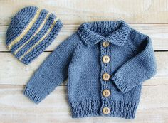 """This hat and sweater set will fit infant boys up to 9 months old.    Hand knitted from soft and cozy cotton yarn in denim blue, this sweater features wooden buttons, and comes with a matching hat with yellow stripes.  Perfect gift idea for a shower or to welcome a new baby.    Sweater measures 10"""" high, 10"""" from neckline to cuff, and 9"""" across chest.  Hat is 6"""" high and 7"""" wide at brim.  Hand wash, dry flat."""