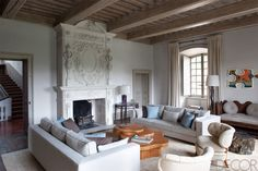 The living room of Pierre Yovanovitch's 17th-century château is the epitome of streamlined chic. The custom-made sofas are covered in a Rogers & Goffigon linen, the circa-1940s armchairs are by Otto Schultz, and the cocktail table is a 1949 design by T. H. Robsjohn-Gibbings. See the rest of the home.   - ELLEDecor.com