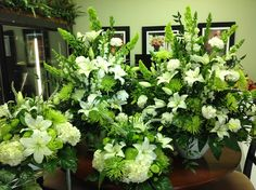 Guest table arrangements and ceremony arrangements.  Cool green and white.  Yummy!