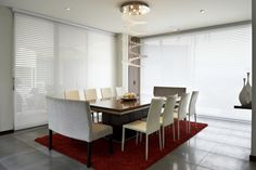 Modern dining room with large windows and a lovely centre chandelier #diningrooms #blinds #lighting