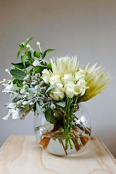 A gorgeous bouquet of white ice protea, roses, bouvardia, tetra nut and silver suede arranged in a large fishbowl vase. Perfect to take home or give as a gift. $75.