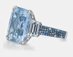 A 17.56-carat pale blue Burmese sapphire is accented with two trapezoid diamonds and microset with white diamonds and blue sapphires.