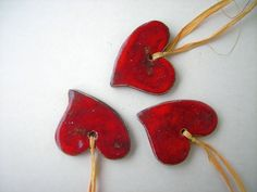 **Set: 3 rotglasierte Herzen aus Keramik mit Bastbändchen.**  Die etwas schiefen Herzen sind mit schöner roter Glasur versehen, und sind mit einem naturfarbenen Bastbändchen versehen. Die...