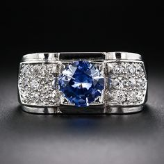 A sizzling cornflower blue faceted round sapphire, weighing 1.73 carats, with subtle lavender overtones, is the center of attention of this sleek and chic Art Deco ring, beautifully and substantially crafted in platinum - circa 1930s. The rounded shoulders of the streamline moderne mounting sparkle with pave set old mine diamonds terminating in a cut ribbon motif. An indented border adds geometric flair to this bright and beautiful vintage bauble.