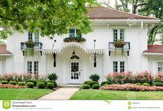 White house with red tile roof,  black metal detail, pink flowers