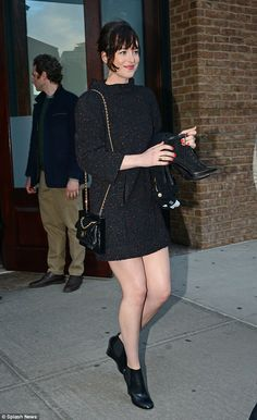 Flirty and fun! Dakota Johnson flashed a coquettish smile as she made her way outside of her hotel in New York on Monday