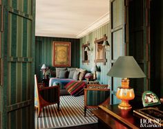 Paris apartment, separated from the dining room by a nailhead-studded folding screen, includes Biedermeier armchairs and a daybed covered by a vintage shawl. The table lamps are from the Madeleine Castaing collection. The sconces are by François Catroux.