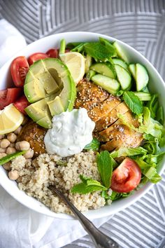 White salad bowl filled with chicken shawarma, quinoa, and salad.