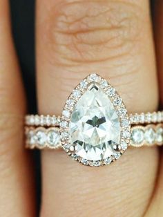 A pear-shaped engagement ring with diamond wedding bands