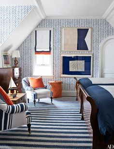 """A graphic <a href=""""http://www.serenaandlily.com/"""">Serena & Lily</a> wallpaper enlivens the boys' room; chairs upholstered in a denim stripe by <a href=""""http://www.ralphlaurenhome.com/"""">Ralph Lauren Home</a> flank an 1870 English chest, the framed naval flags are vintage, and the rug is by Montagne Handwoven."""